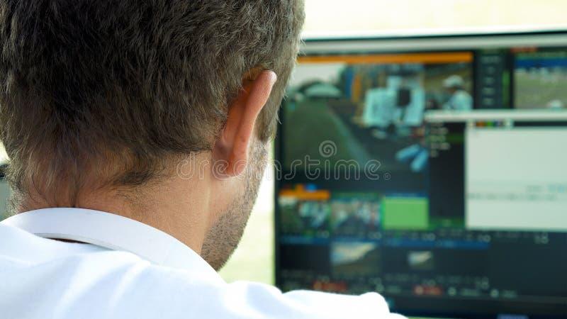 Rédacteur visuel d'émission avec des écouteurs à l'écran images libres de droits