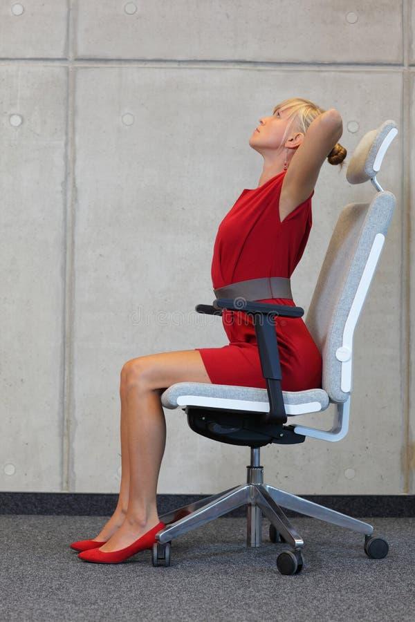 Réduction du stress dans le travail de bureau - femme s'exerçant sur la chaise photo stock