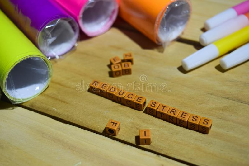 Réduisez l'effort sur les cubes en bois avec le papier et le stylo colorés, inspiration de concept sur le fond en bois images libres de droits