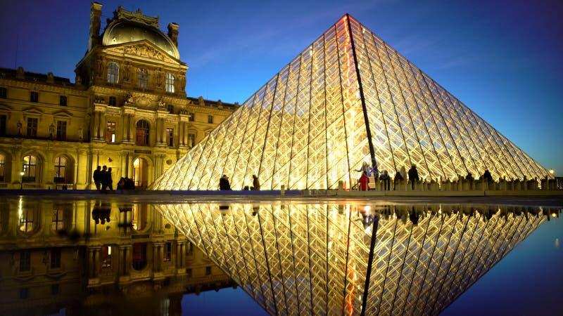 Réflexion étonnante de pyramide lumineuse de Louvre dans l'eau, vues de Paris la nuit image libre de droits