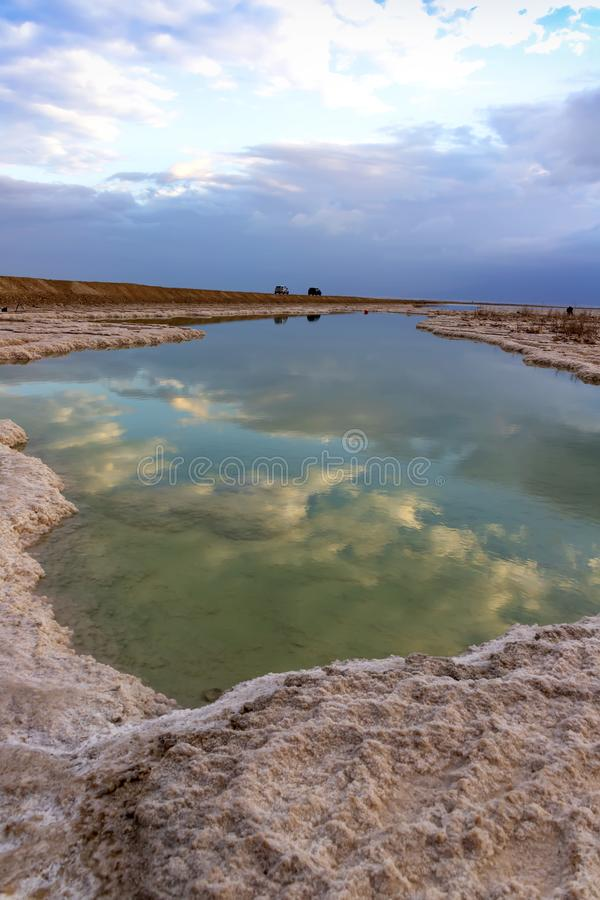 Réflexion d'un ciel nuageux dans l'eau de la mer morte entre les formations de sel au lever de soleil photographie stock