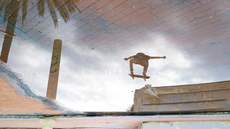 Réflexion d'un patineur sautant image libre de droits