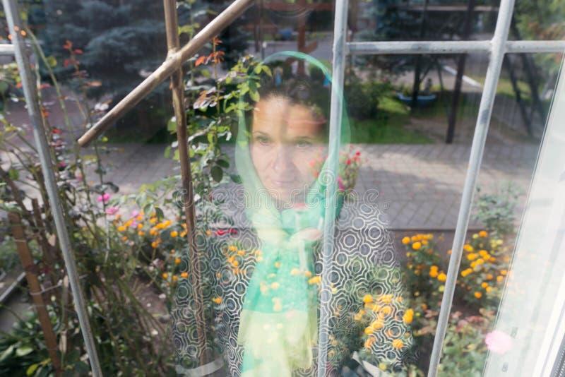Réflexion d'une fille dans une écharpe dans une fenêtre photo libre de droits