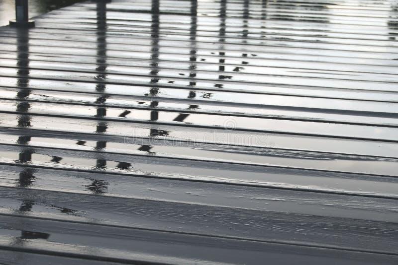 Réflexion dans l'eau sur le plancher piétonnier en bois le jour pluvieux photographie stock libre de droits
