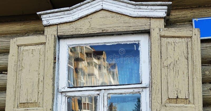 Réflexion dans le verre de la fenêtre de la vieille maison du nouveau bâtiment photographie stock