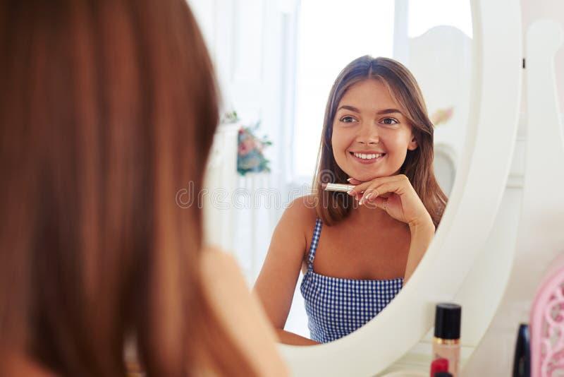 Réflexion de belle fille dans le miroir tenant le rouge à lèvres images stock