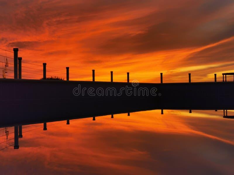 Réflexion de coucher du soleil de stupéfaction sur la piscine images stock