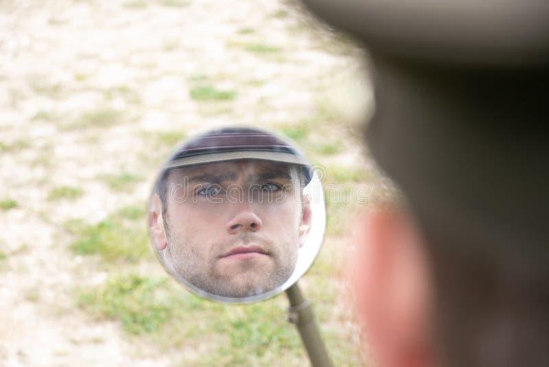 Réflexion de dirigeant d'armée beau de GI de l'Américain WWII dans le miroir d'aile de véhicule image stock