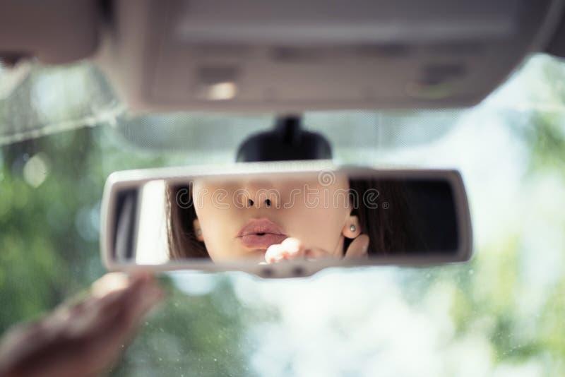 Réflexion de jeune femme envoyant le baiser d'air tout en conduisant la voiture dans le miroir de vue arrière photographie stock