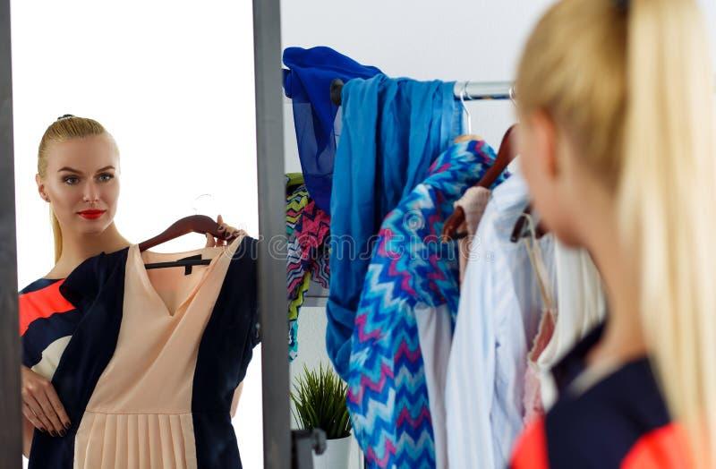 Réflexion de la belle femme blonde essayant la nouvelle robe images stock