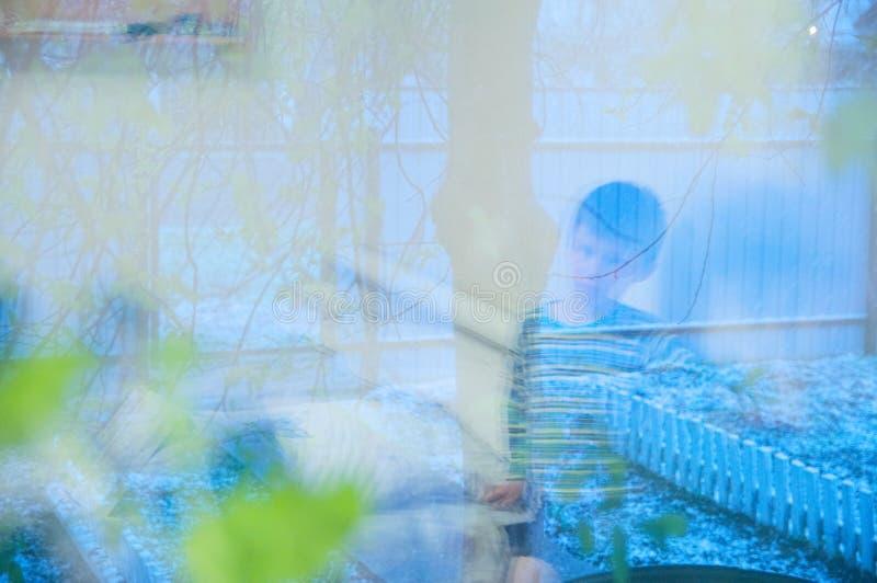 Réflexion de maison d'emplacement de garçon sur le désir ardent de fenêtre de marcher et de jouer extérieur Temps froid de neige  photos stock