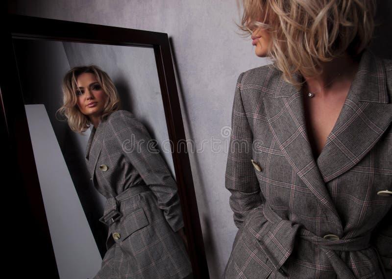 Réflexion de miroir de femme blonde se penchant contre un mur photographie stock libre de droits