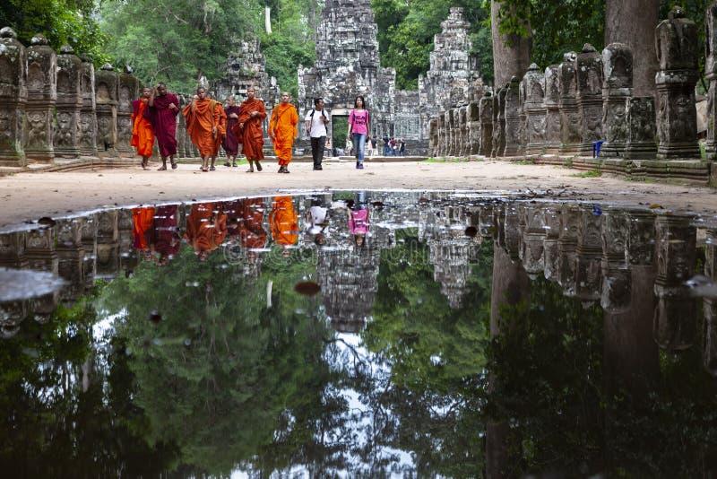 Réflexion de moines bouddhistes sur l'eau photographie stock