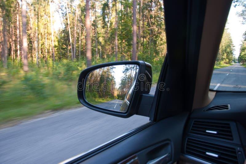 Réflexion de route dans la forêt au miroir de côté de voiture images stock