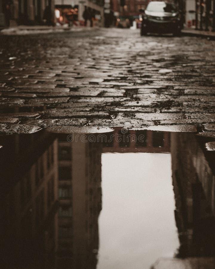 Réflexion de rue de pavé rond dans le village occidental images stock
