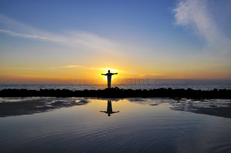 Réflexion des bras ouverts de l'homme faisant face au soleil se tenant sur la barrière de vague photos stock