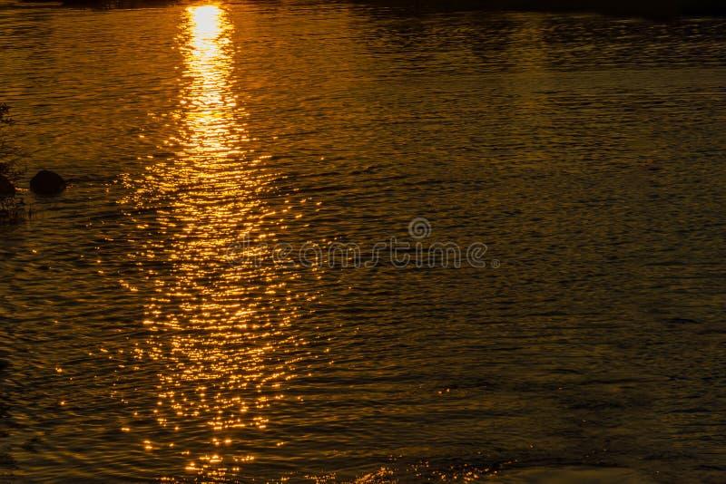 Réflexion des rayons du coucher de soleil sur la surface de l'eau Texture de l'eau Fond naturel photographie stock libre de droits