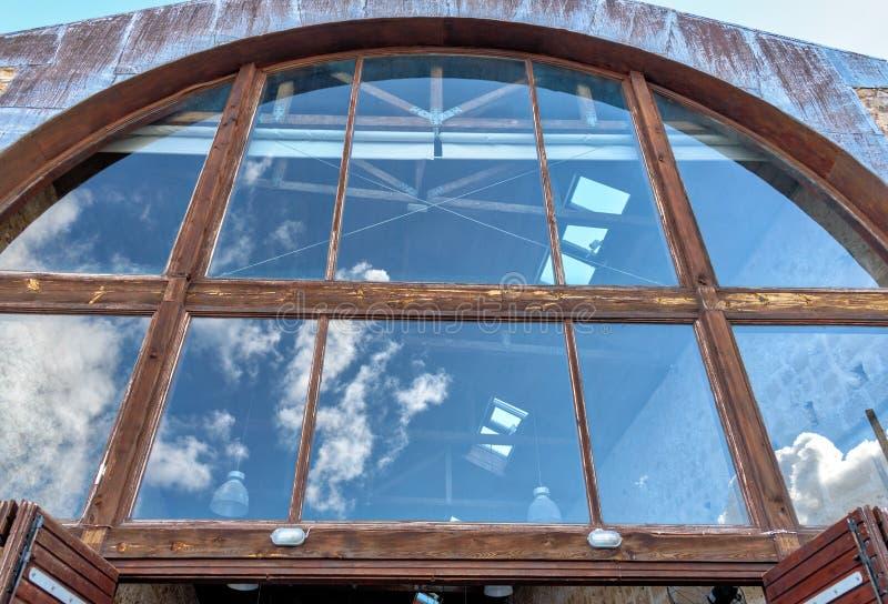 Réflexion du ciel dans la vieille grande fenêtre photographie stock