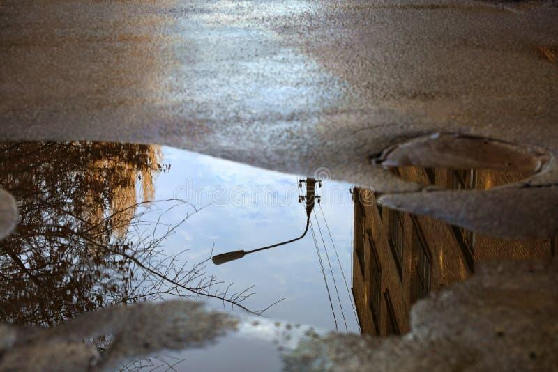Réflexion du ciel, de la silhouette d'un réverbère et d'un arbre ensoleillé dans un magma sur l'asphalte photo stock
