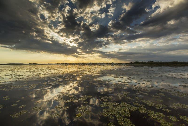 Réflexion orageuse sinistre de ciel au-dessus de lac naturel photo stock