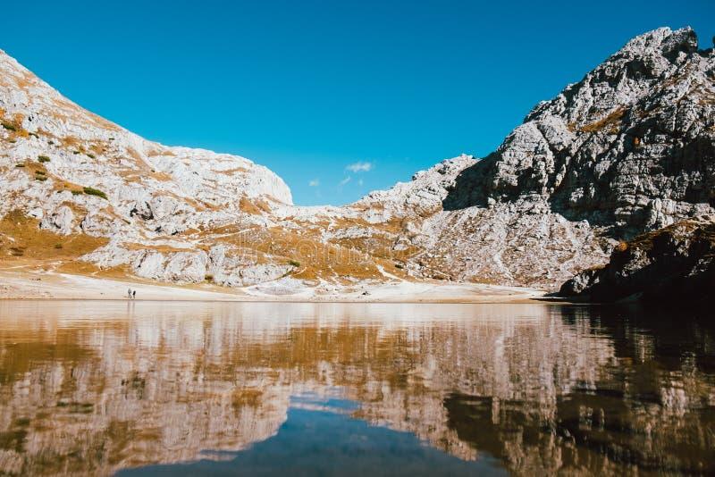 Réflexion parfaitement symétrique dans le lac propre de montagne dans les alpes italiennes avec l'eau transparente claire et le c photo libre de droits