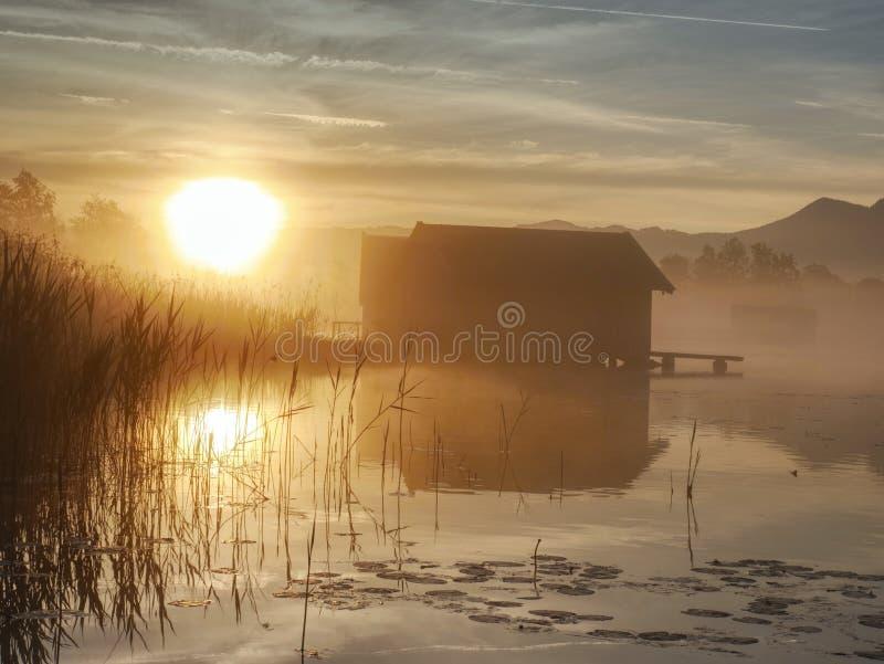 Réflexion romantique de lever de soleil sur le lac Kochelsee contre des hangars à bateaux photo libre de droits