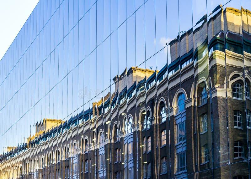 Réflexion victorienne de maison dans un bâtiment en verre moderne dans la grande ville photos stock