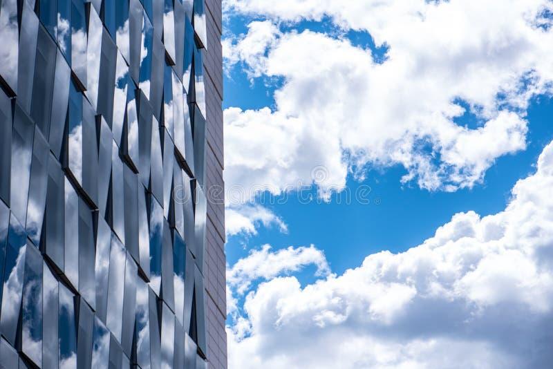 Réflexions de ciel nuageux sur une façade en verre images libres de droits