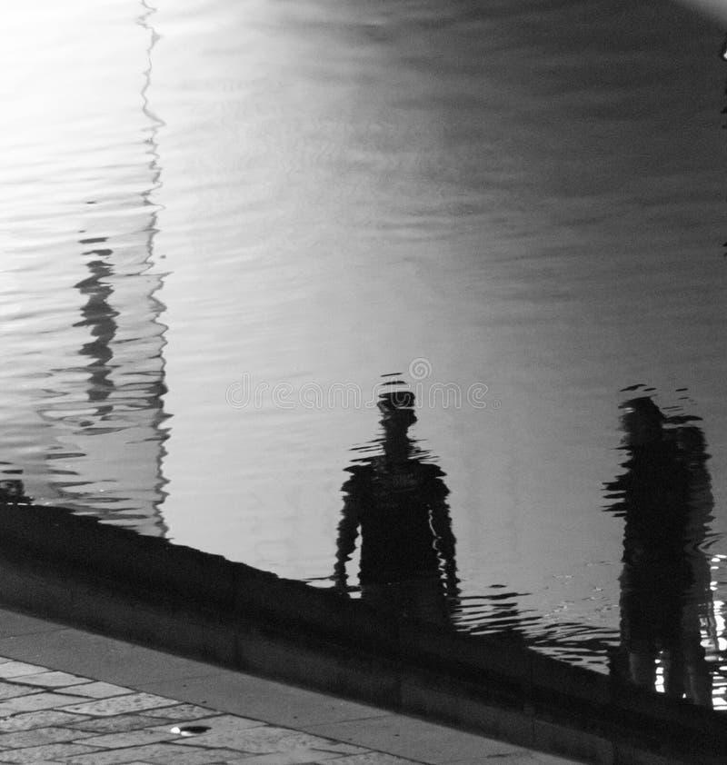 Réflexions de deux personnes sur la surface ondulée d'un canal dans t photographie stock