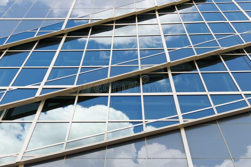 Réflexions de nuages sur le bâtiment en verre moderne image libre de droits