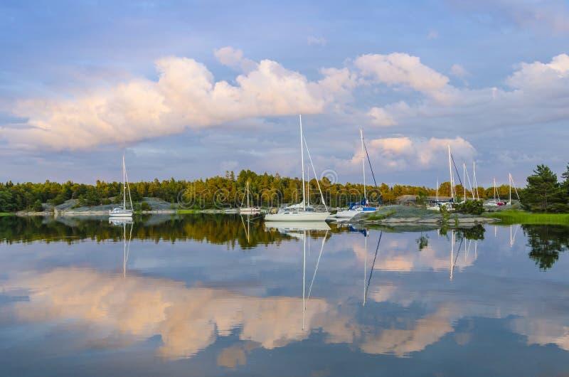 Réflexions de Sailingbotas dans l'eau Harstena Suède images stock