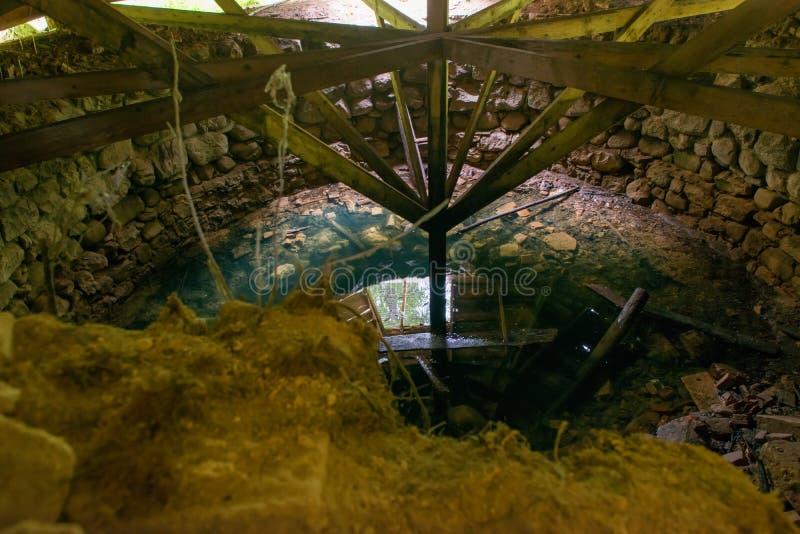 Réflexions sur la surface de l'eau dans un vieux puits détruit photographie stock libre de droits