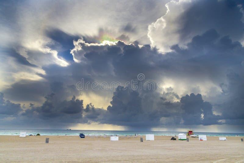 Réfractions légères dans les nuages foncés à la plage du sud images stock