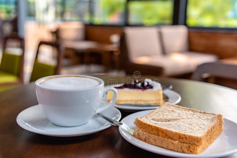 Régénération et petit déjeuner délicieux avec le latte de café, le sandwich à thon et le pin de fromage de myrtille dans le café image stock