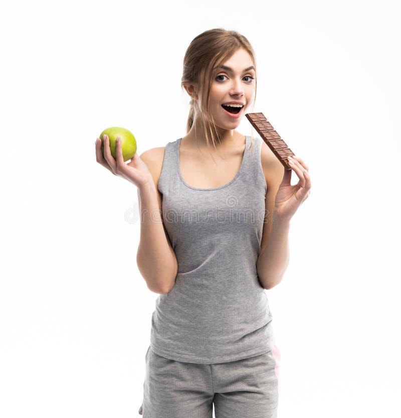 Régime Concept suivant un régime Nourriture saine Belle jeune femme choisissant entre la nourriture saine et malsaine Fruits ou b images libres de droits