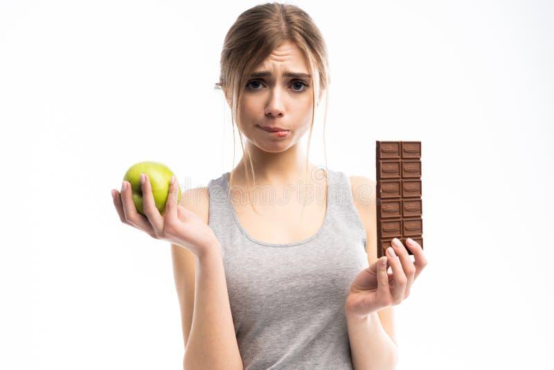 Régime Concept suivant un régime Nourriture saine Belle jeune femme choisissant entre la nourriture saine et malsaine Fruits ou b images stock