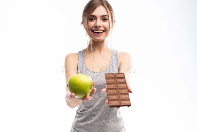 Régime Concept suivant un régime Nourriture saine Belle jeune femme choisissant entre la nourriture saine et malsaine Fruits ou b photos stock