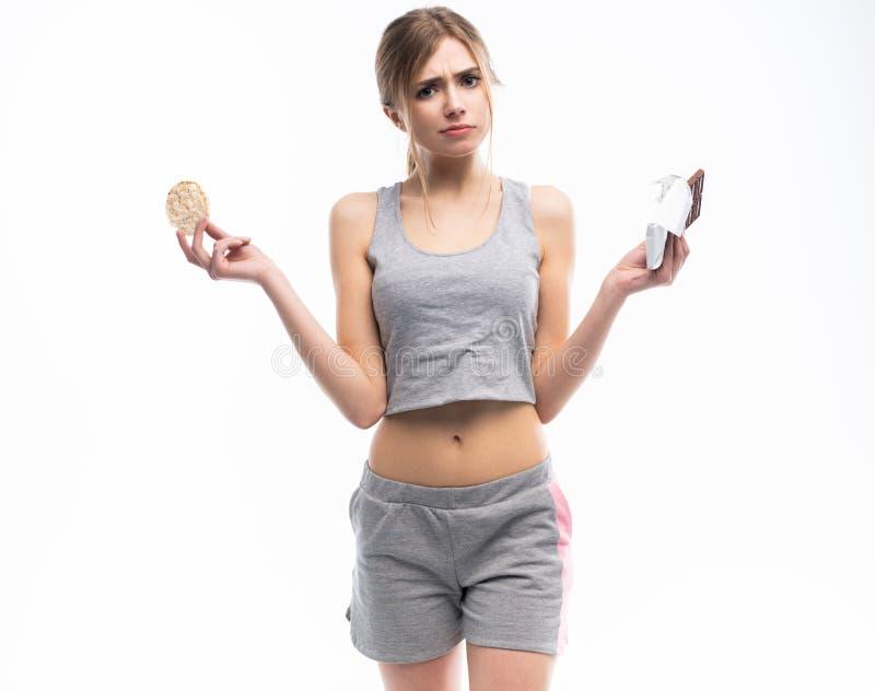 Régime Concept suivant un régime Nourriture saine Belle jeune femme choisissant entre la nourriture saine et malsaine Fruits ou b image libre de droits