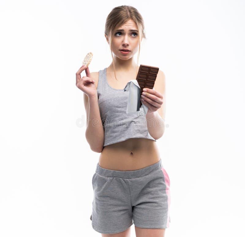 Régime Concept suivant un régime Nourriture saine Belle jeune femme choisissant entre la nourriture saine et malsaine Fruits ou b photo stock