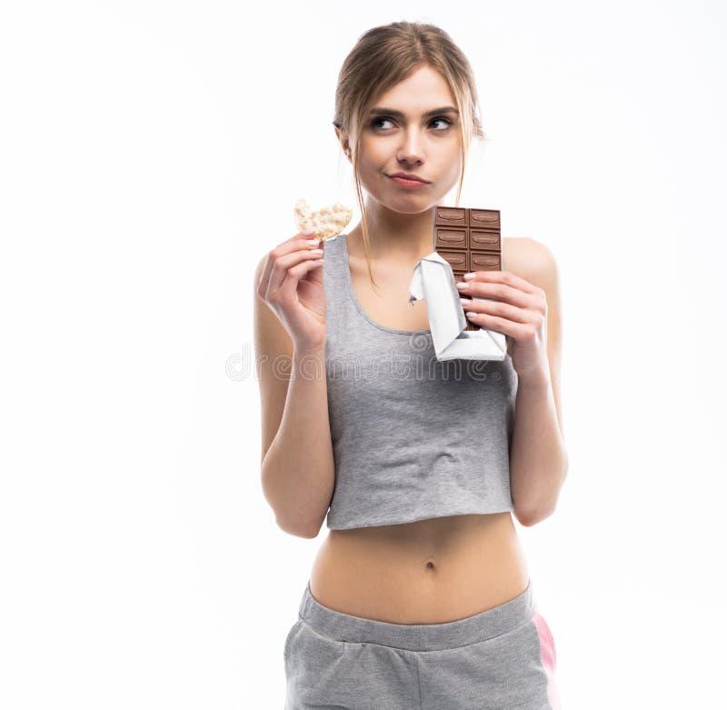 Régime Concept suivant un régime Nourriture saine Belle jeune femme choisissant entre la nourriture saine et malsaine Fruits ou b photos libres de droits