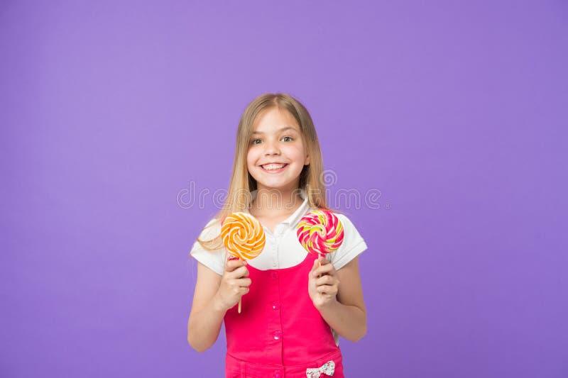 Régime et suivre un régime Sourire de fille avec des lucettes sur le fond violet Enfant heureux avec des caramels Petit enfant av photos stock