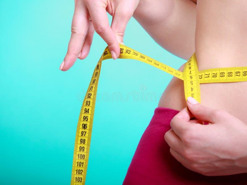 Régime. Fille convenable de femme de forme physique avec la mesure de bande de mesure sa taille photos stock