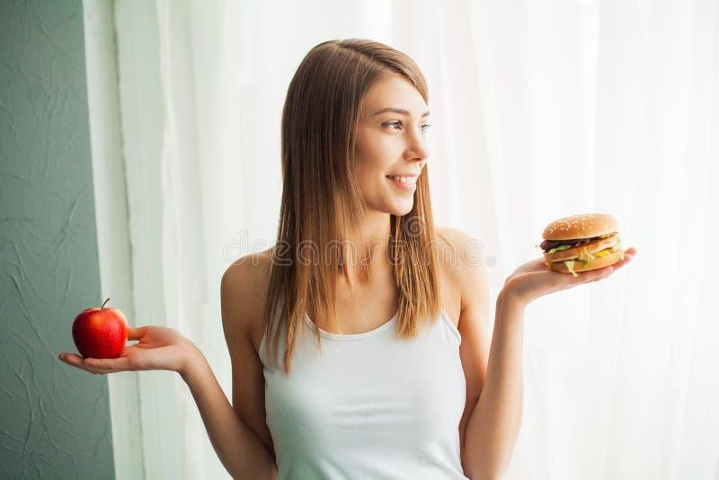 Régime Le concept de la nutrition saine et malsaine Le modèle plus la taille fait un choix en faveur de la nourriture saine et photos libres de droits