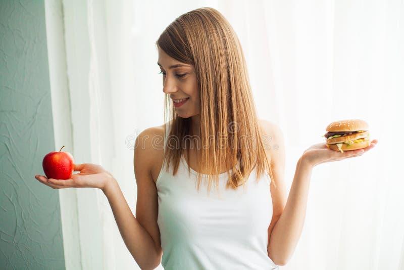 Régime Le concept de la nutrition saine et malsaine Le modèle plus la taille fait un choix en faveur de la nourriture saine et image libre de droits