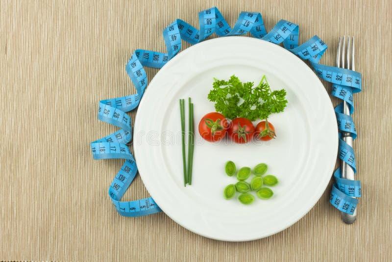 Régime strict contre l'obésité Régime végétal diététique Tomates d'un plat Légumes crus sur un plat blanc et une bande de mesure photo stock