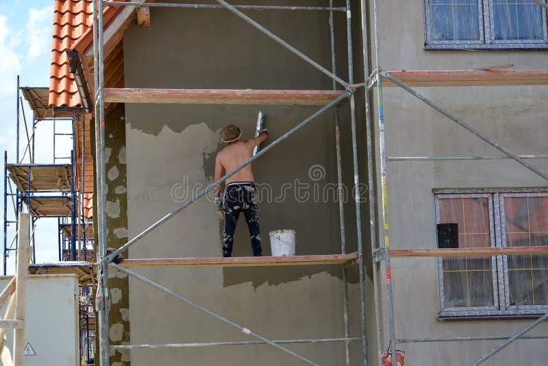 Région de Kaliningrad, Russie Le travailleur plâtre une façade de cottage, se tenant sur les bois de construction photos libres de droits