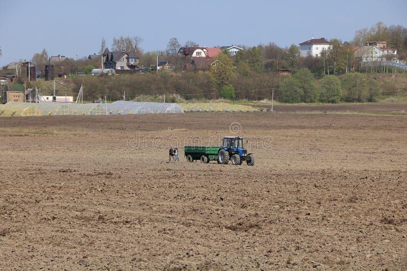 Région de la Russie, Léningrad, le 1er mai 2019, village russe Le village russe au printemps et le tracteur qui laboure le champ image stock