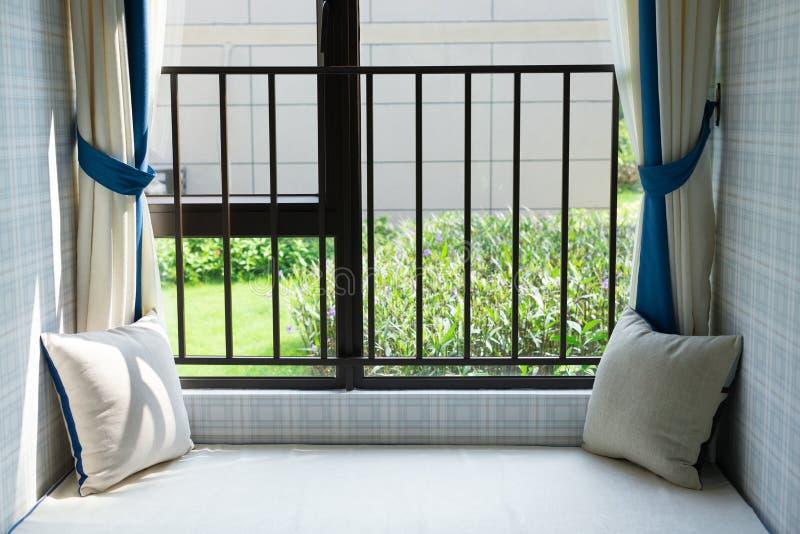 Région de repos d'un siège fenêtre confortable avec le coussin vert le matin horizontal image stock
