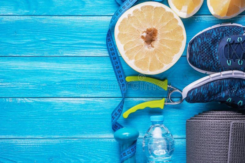 Réglé pour des activités de sports sur le fond en bois bleu Concept sain de style de vie Équipement de sport, tapis de yoga, chau photos stock