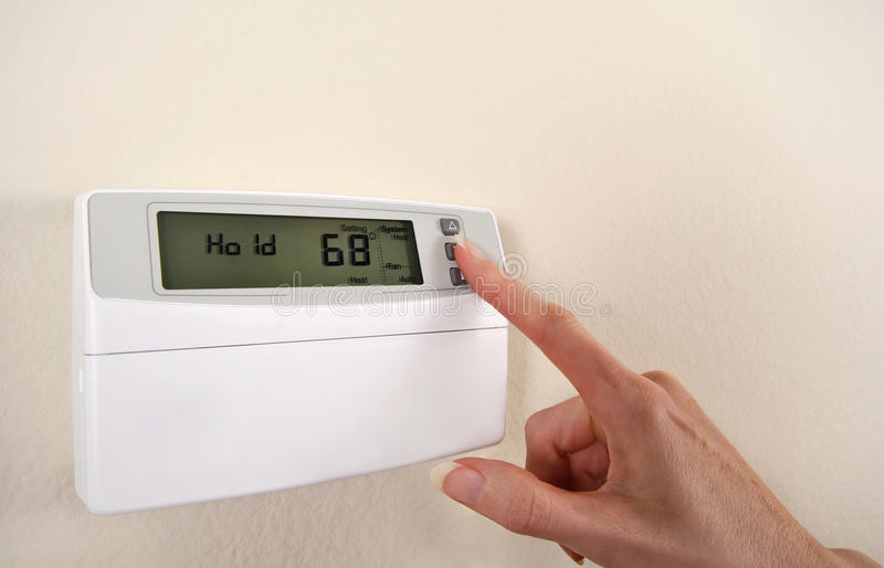Réglant et plaçant le thermostat images stock